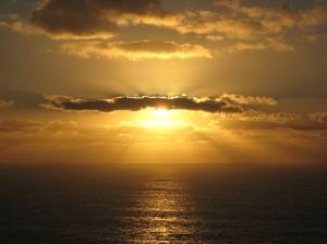 Un soleil couchant, au dessus de la mer et derrière les nuages.